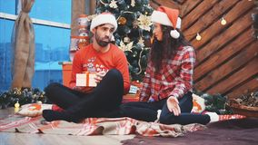 Video fHD of affectionate girl giving Christmas present to her boyfriend but she doesn`t get anything in return.