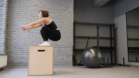 This video is about Fit Athletic Caucasian Woman Does Box Jumps in the Gym. Intense Exercise is Part of Her Daily Fitness Training stock video