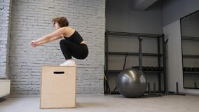 This video is about Fit Athletic Caucasian Woman Does Box Jumps in the Gym. Intense Exercise is Part of Her Daily Fitness Training. Program. Side view stock video footage