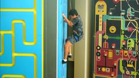 Boy climbing a wall indoor. Video footage of attractive little boy climbing a wall indoor while wearing a safety rope to train his courage, strength, endurance stock video