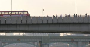 London Bridge business commuters and traffic. Video footage of business commuters and road traffic passing over a busy London Bridge during a dusky late stock video