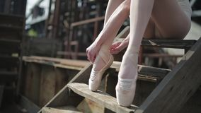 Video footage close-up of a ballet dancer tying. Video footage close-up of a ballet dancer sitting tying ribbons on pointe stock footage