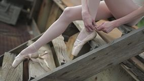 Video footage close-up of a ballet dancer tying stock footage