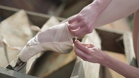 Video footage close-up of a ballet dancer tying stock video footage