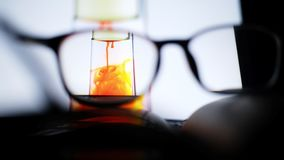 Video footage of red food color ink drop from oil into water in clear  test tube looking through nearsighted eye glasses. Close up, full high definition stock video