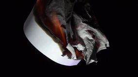 White Paper Burning. This video footage shows a close-up of a burning white sheet of paper. This shows that the paper is smoldering and the ashes are falling stock video