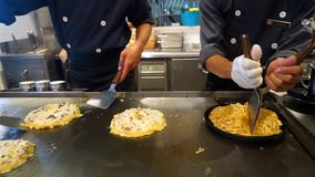 Two chef making omelet in the kitchen. Video footage of two male chef making omelet with noodle in the restaurant kitchen stock video footage