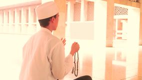 Muslim man praying with beads in mosque stock video