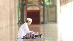 Muslim man reading Quran in Istiqlal mosque stock video footage
