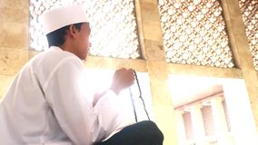 Muslim man holds prayer beads in mosque stock video footage