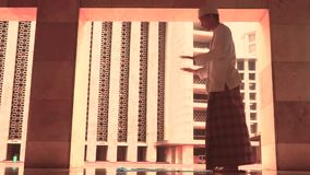 Muslim person praying in Istiqlal mosque stock video