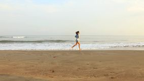 Woman running on beach in the morning. Video footage of a young woman running on the tropical beach in the morning stock footage