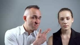 Video of fun and grimacing man on grey background. Video of man and woman sitting near on grey background stock video footage