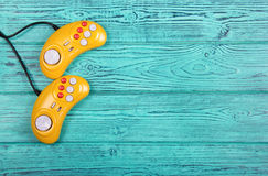Video game console GamePad on a old blue wooden background table. Yellow retro GamePad. Royalty Free Stock Photography