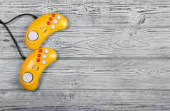 Video game console GamePad on a old gray wooden background table. Yellow retro GamePad. Copy space. Royalty Free Stock Photo