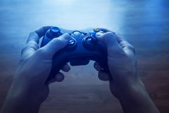 Video game controller in human hands, in front of the TV stock photography