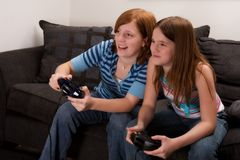Video Game Fun. Two preteen girls at home playing an exciting video game Stock Photos