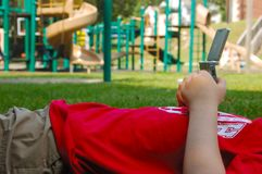 Video Game at the Playground. Young boy plays with a hand held video game while  lying on the ground.  There is a playground in the background.  He is wearing a Stock Images