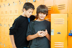 Video Game in School. Two teenage boys playing a handheld video game in school by their lockers Royalty Free Stock Images