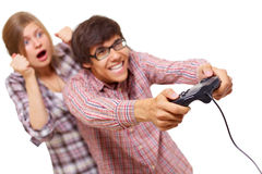 Video game teens. Happy teenager in checked shirt and black glasses playing video game with passion and his girlfriend supports him. Focus on joystick, mask Royalty Free Stock Image