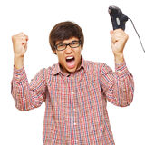 Video game winner. Happy young man in winning pose in glasses wearing shirt holding video game joystick over isolated background. Mask included Stock Photography