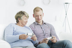 Video games are for everyone. Elderly women and young men sitting on a sofa, holding gamepads Royalty Free Stock Photo