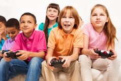 Video games are fun. Close portrait of a group of diversity looking kids, boys and girls playing videogame Royalty Free Stock Photo