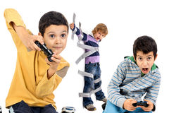 Video games time. Boys playing video games and young brother glued to the wall with duct tape in the background Royalty Free Stock Photography