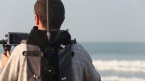 Video gente della fucilazione dell'operatore con il sistema di stabilizzazione sulla spiaggia video d archivio