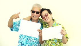 Video Happy Asian senior couple holding white blank sign ready for holiday trip stock video footage
