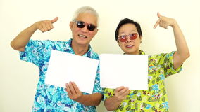 Video Happy Asian senior couple holding white blank sign ready for holiday trip stock video