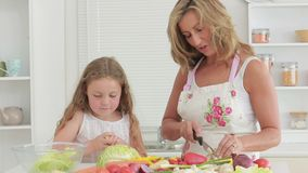 Video of happy mother cutting vegetables stock video