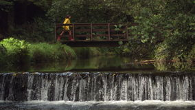 Video of idyllic waterfall with brunette running over bridge stock video footage