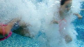 video 4k av dykning för tonårs- flicka under vatten i simbassäng Beskåda från under vattenyttersidan arkivfilmer