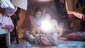video 4k av läseboken för två flickor aloud på detgjorda tältet lager videofilmer
