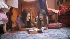 video 4k av två gulliga systrar som ligger på golv och läseboken med ficklampan arkivfilmer