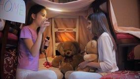 video 4k av två systrar i pyjamas som berättar berättelser med ficklampan på natten lager videofilmer