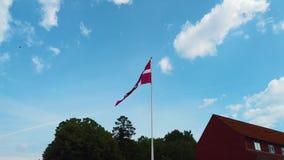 video 4K del Danese della bandiera della Danimarca che soffia nel cielo blu È situato nel centro di Copenhaghen stock footage