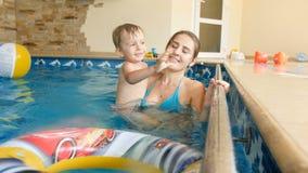 video 4k del ragazzo sorridente adorabile del bambino con nuoto della madre nello stagno un thouse video d archivio