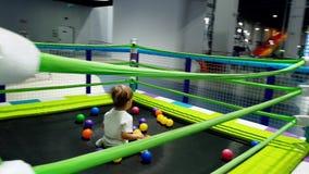 video 4k del ragazzo sorridente allegro del bambino che salta sul trampolino sul campo da giuoco al centro commerciale video d archivio