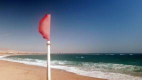 video 4k della bandiera rossa d'ondeggiamento il giorno tempestoso alla spiaggia del mare video d archivio