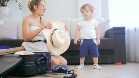 video 4k della madre con le cose dell'imballaggio del figlio del bambino in valigia stock footage