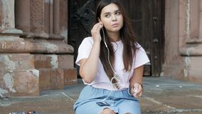 video 4k della ragazza castana sorridente che si siede sulla scala di pietra e sulla musica d'ascolto con le cuffie sul telefono  video d archivio