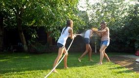 Video 4k der glücklichen jungen Familie, die Wasserkampf am heißen sonnigen Tag im Garten hat stock footage