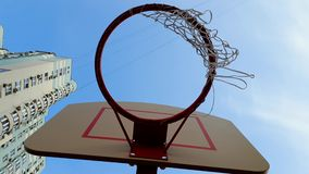 Video 4k des Basketballringes gegen blauen Himmel und hohes Gebäude Korb mit Netz für werfenden Ball im Bezirk stock video footage