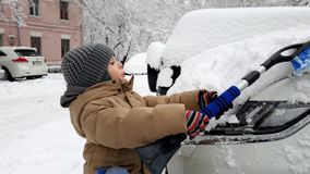Video 4k des Kleinkindjungen-Reinigungsautos vom Schnee mit Bürste Kind, das Fahrzeug am Morgen nach Blizzard säubernd hilft stock video footage