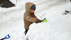 Video 4k des Kleinkindjungen-Reinigungsautos vom Schnee mit B?rste Kind, das Fahrzeug am Morgen nach Blizzard s?ubernd hilft stock footage