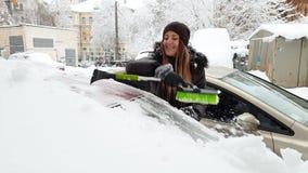 Video 4k des sch?nen weiblichen Fahrers, der ihr Auto vom Schnee nach Blizzard am Morgen s?ubert stock video footage