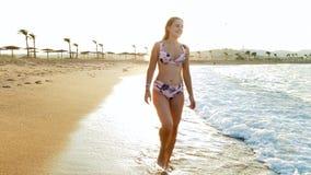 video 4k di bella donna sorridente in bikini che cammina sulla spiaggia al tramonto stock footage