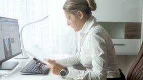 video 4k di bella giovane donna di affari che lavora con i documenti e che scrive sul computer all'ufficio archivi video